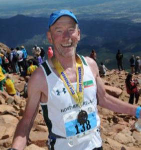 Peter with his '2014 Finisher' medal at the summit of Pikes Peak